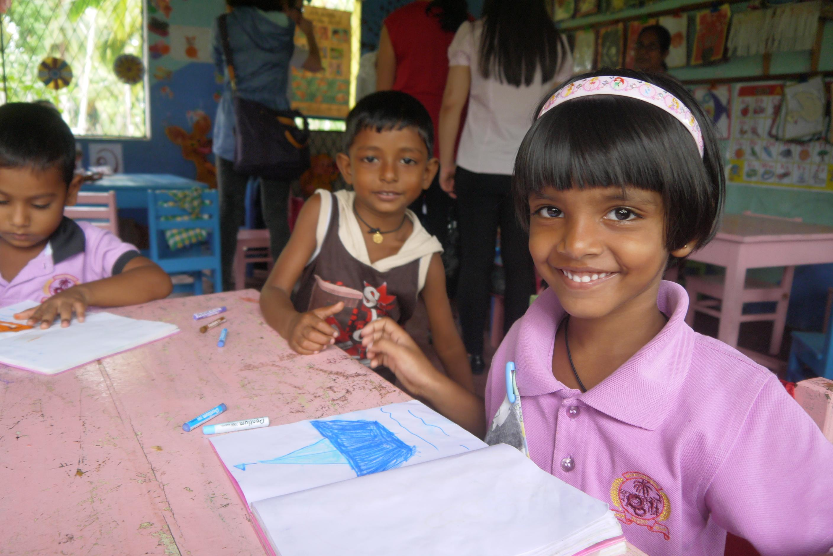 Children smile at the camera while doing their homework at our volunteer teaching placements in Sri Lanka